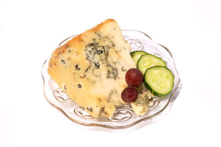 plater: wedge of ripe Stilton Cheese with cucumber and grapes Stock Photo
