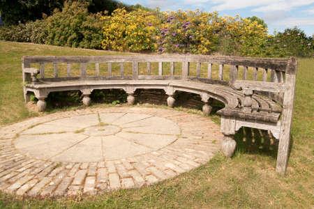 Circular wooden bench surrounding a large brick circle photo