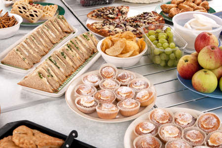 spread: Food spread out over table in preparation of a picnic