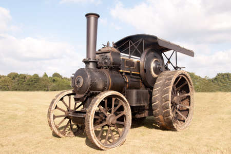 old farm: Old fashioned steam tractor standing in a field