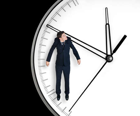 Businessman hangs on an arrow of clock, isolated on black background