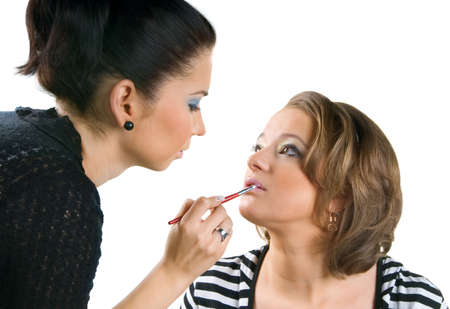 concealer: Makeup artist applying lipstick using lip concealer brush, isolated on white background