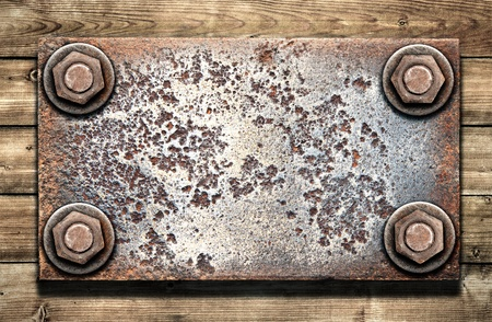 Old metal plate on  wooden wall photo