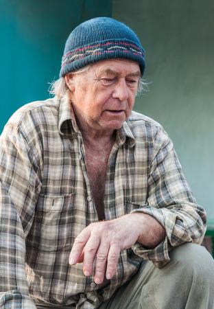 sad look: Seniors retrato de contemplativo hombre caucásico de edad mirando hacia abajo. Foto de archivo