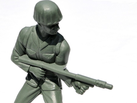Close-up action toy soldier, isolated on white.