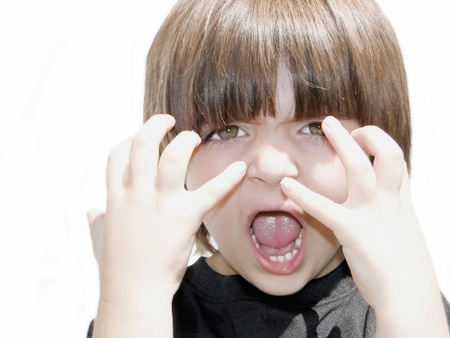 An angry little boy, isolated on a white background. Stock Photo