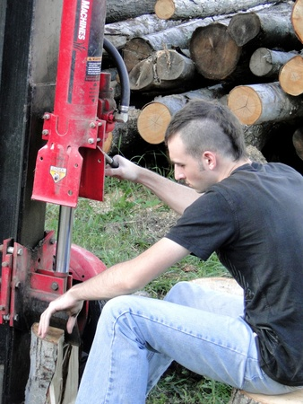 Young man chopping wood, with a log splitter.