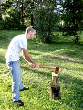 Young man chopping wood with an ax.