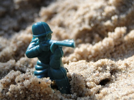 Toy green soldier in the sand box.
