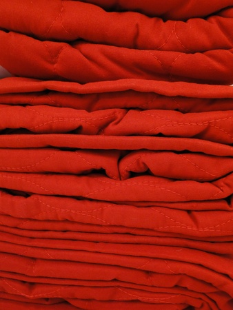 Red towels stacked filling the frame. Stock Photo