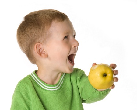 The kid holds an apple in hands and is dared Stock Photo - 1510864