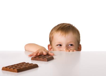 El ni�o intenta guardar paso con un chocolate que pone en una tabla