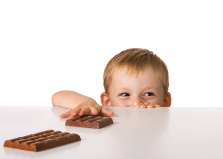The child tries to keep step with a chocolate laying on a table