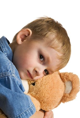 Sad kid embraces a teddy bear photo