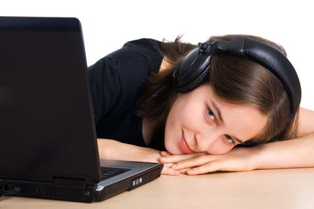 Smiling girl listening to music on a laptop computer  photo