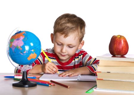 Little boy sitting by his desk with a red apple on pile of books