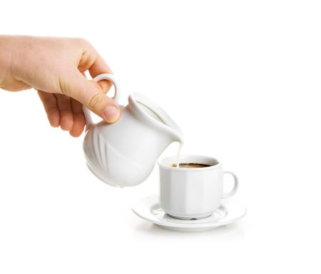 Milk stream flowing down in cup of coffee photo