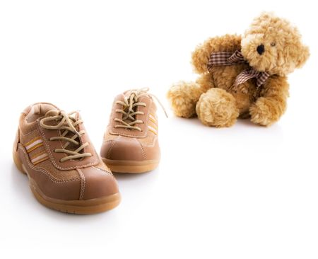 Childrens brown shoes and teddy bear photo