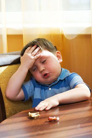 sick kid: Enfermo chico toca un frente caliente una mano