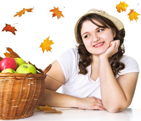 Pretty girl with basket of apples and maple leaves photo