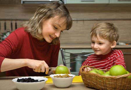 Mother with son is eaten fruit in kitchen photo