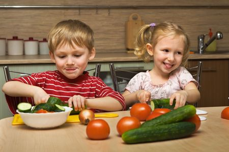 Small boy and girl cut vegetables