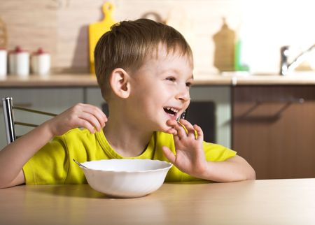 sitting at table: Child eating breakfast Stock Photo