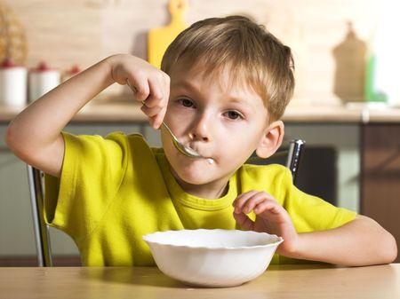 Joyful breakfast of little boy