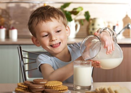 milk and cookies: Healthy child pours milk from jug