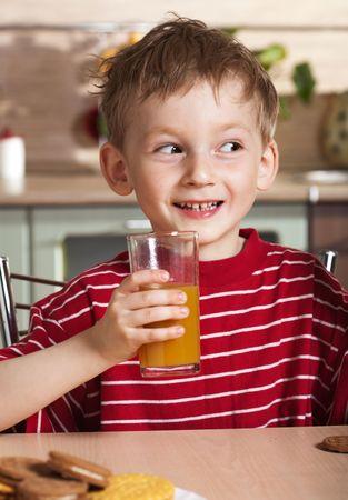 Bambino beve succo d'arancia Archivio Fotografico