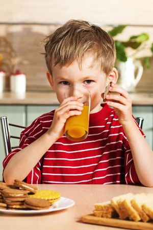 Child drinking orange juice photo