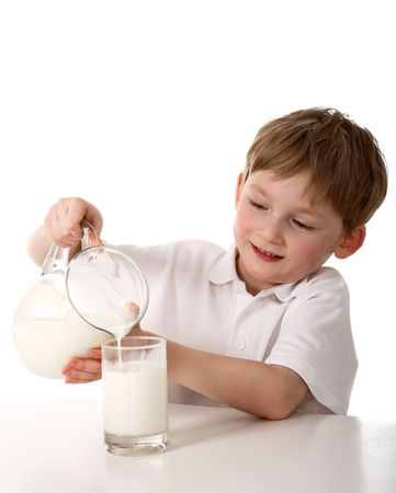 Kid pours milk Stock Photo