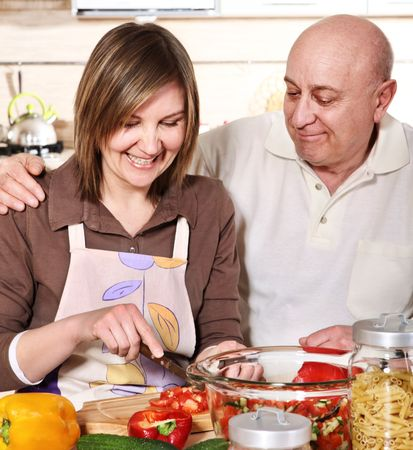 Senior smiling couple cooking at kitchen photo