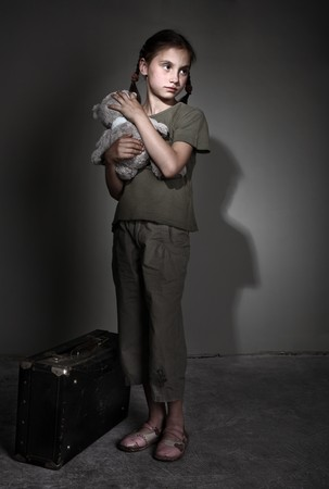neglect: Little lonely girl with suitcase Stock Photo