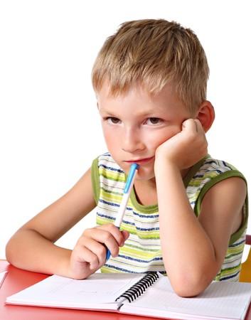 Sad schoolboy doing homework