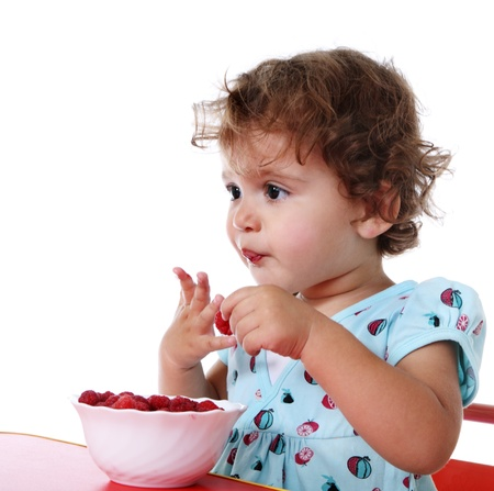 Baby girl eat raspberry Stock Photo