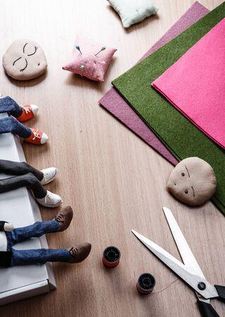 Process of making dolls. Scissors, colored felt, thread. Top view.