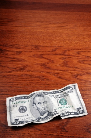 five dollars: Five-dollar bills on a wooden table Editorial