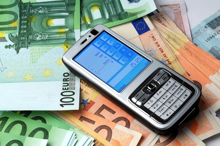 Mobile phone on money background, business concept photo