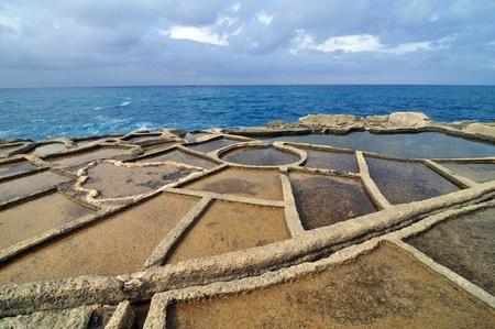 evaporacion: Salinas de evaporaci�n de la costa de Gozo, Malta Foto de archivo
