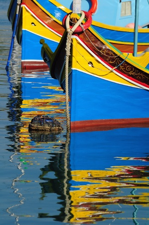 Traditional Maltese fishing boats with reflection photo