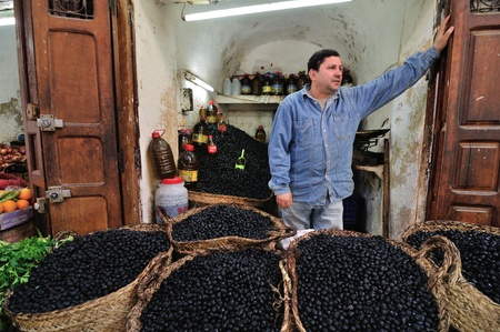 FES - MARCH 10: Unknown man trades a olives in a Market (souk) in a city Fes in Morocco. The market is one of the most important attractions of the city. March 10, 2012 Fes, Morocco. Stock Photo - 15902539