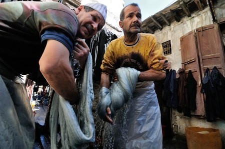 FES - MARCH 10: Two unknown people works to wash thread in a Market (souk) in a city Fes in Morocco. The market is one of the most important attractions of the city. March 10, 2012 Fes, Morocco. Stock Photo - 16205718