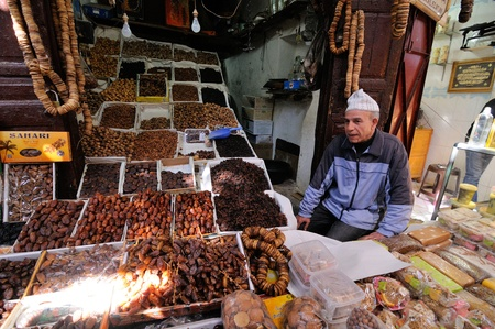 fes: FES - MARCH 10: Unknown man trades a dried Fruits in a Market (souk) in a city Fes in Morocco. The market is one of the most important attractions of the city. March 10, 2012 Fes, Morocco.