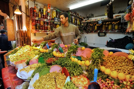 FES - MARCH 10: Unknown man trades a green olives in a Market (souk) in a city Fes in Morocco. The market is one of the most important attractions of the city. March 10, 2012 Fes, Morocco. Stock Photo - 16532398