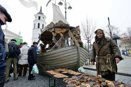 VILNIUS, LITHUANIA - MARCH 1: Unidentified people trades the smoked fish in annual traditional crafts fair - Kaziuko fair on Mar 1, 2013 in Vilnius, Lithuania Stock Photo - 18328946