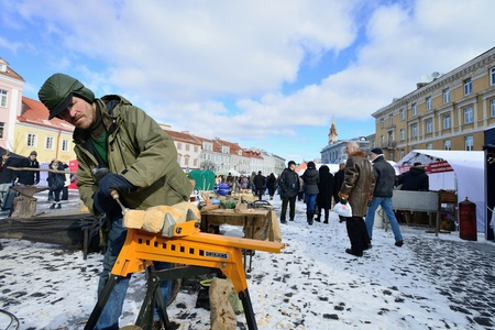 tradespeople: VILNIUS, LITHUANIA - MARCH 2: Unidentified people carve wood sculpture in annual traditional crafts fair - Kaziuko fair on Mar 2, 2013 in Vilnius, Lithuania