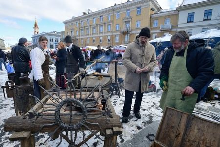 tradespeople: VILNIUS, LITHUANIA - MARCH 2: Unidentified people trades traditional metal decoration in annual traditional crafts fair - Kaziuko fair on Mar 2, 2013 in Vilnius, Lithuania