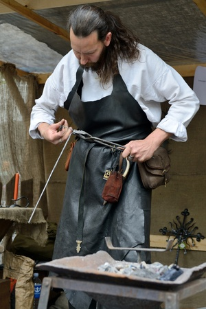 medieval blacksmith: VILNIUS, LITHUANIA - MAY 24 : A blacksmith in medieval clothes, working in the street during a International Folklore Festival on May 24 2013 in Vilnius, Lithuania.
