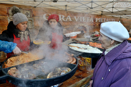 tradespeople: VILNIUS - FEBRUARY 14: Unidentified people trades food on February 14, 2015 in Vilnius, Lithuania. Uzgavenes is a Lithuanian folk festival that start during the seventh week before Easter.